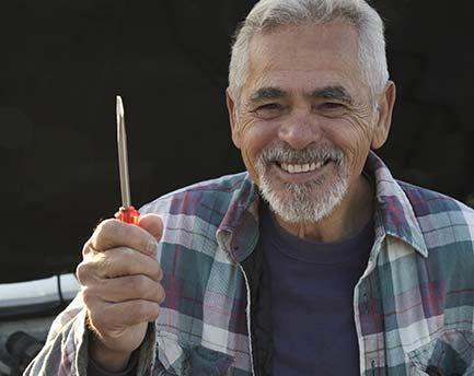 Senior man smiling and holding screwdriver