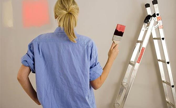 woman decorating at home painting wall holding paintbrush dipped in red paint rear view